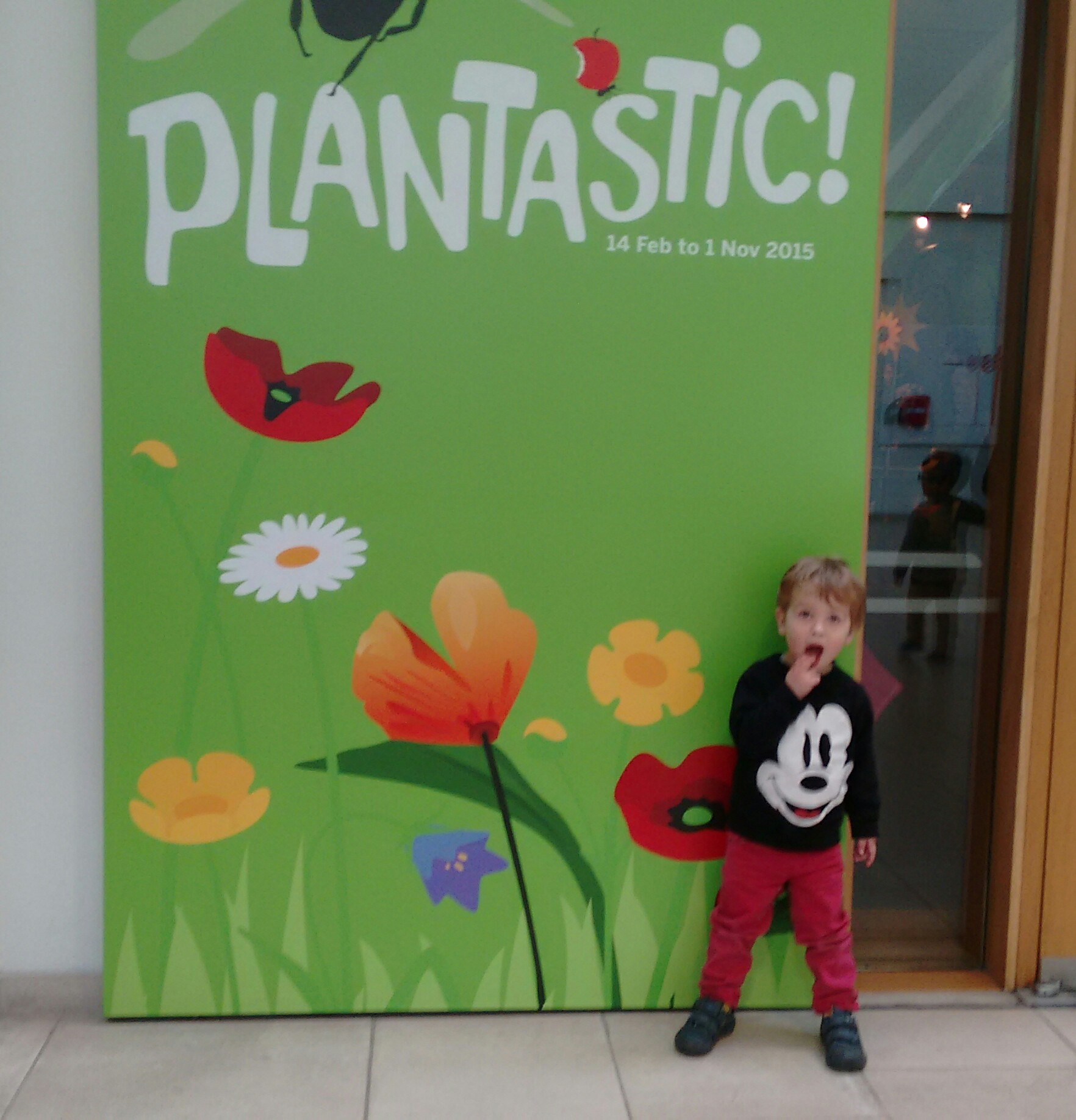 Toddler standing outside sign for Plantastic