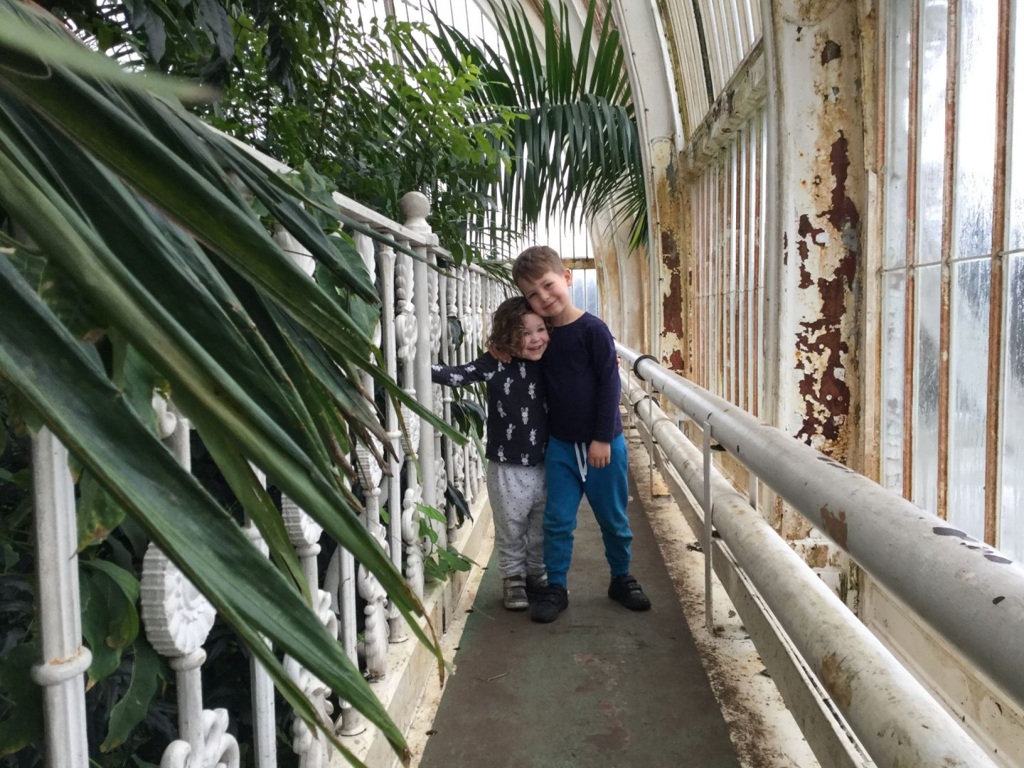 Museum Boy and Girl hug on the iron balcony of the Palm House, Kew Gardens