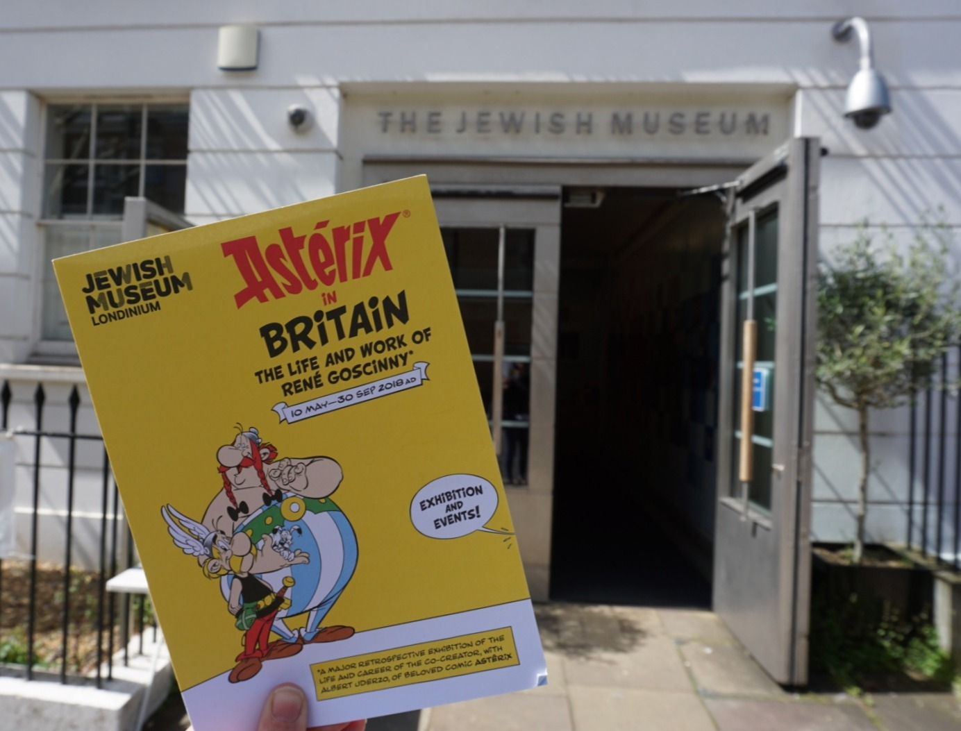 Photograph of Asterix leaflet being held up outside the Jewish Museum London entrance