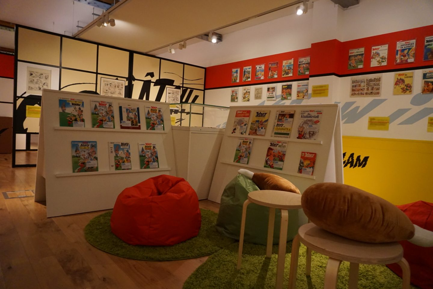 Photograph of family area in the Asterix in Britain exhibition at the Jewish Museum London. You can see bean bags, stools and Asterix comics to read on the shelves