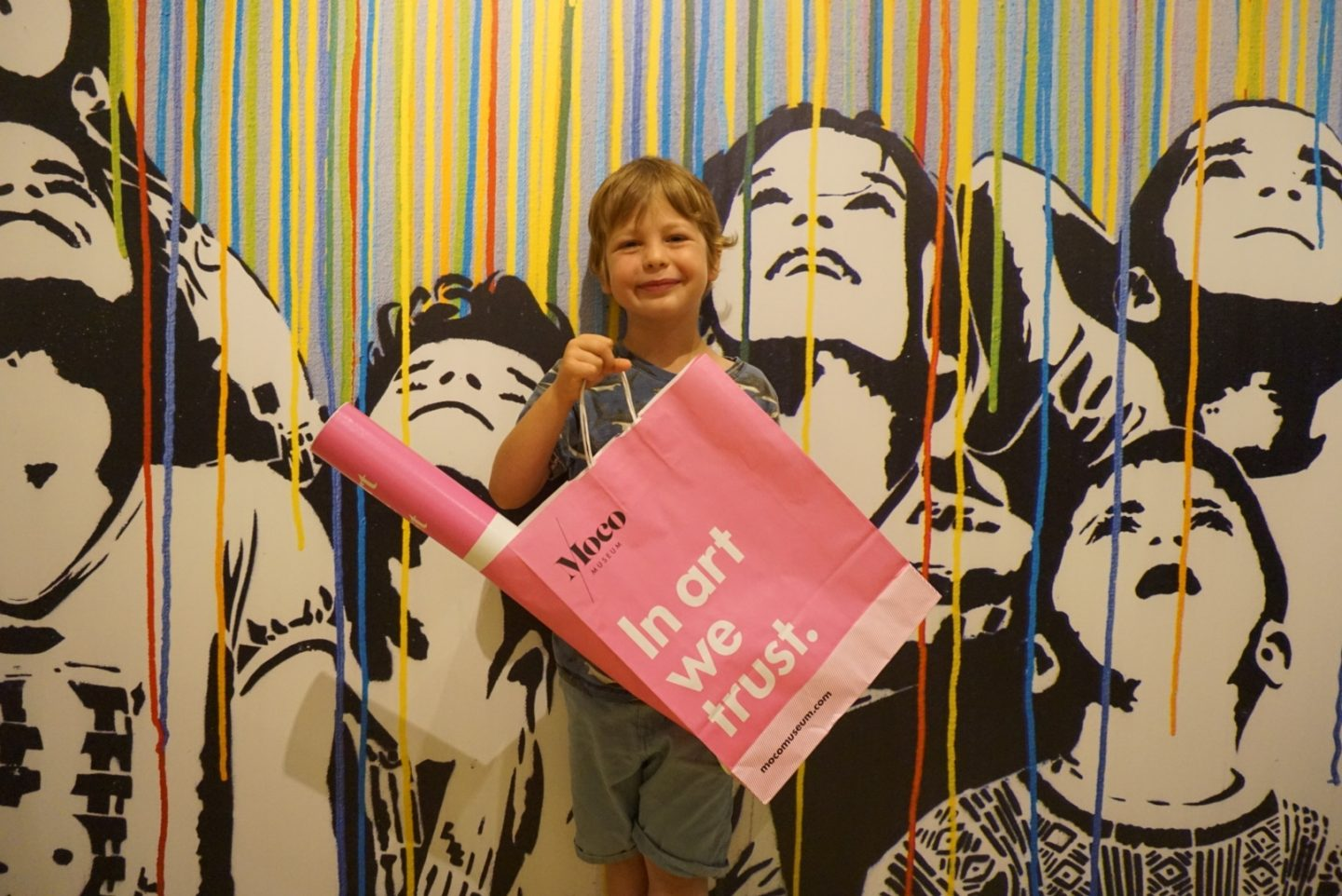 Museum Boy proudly holds up a paper bag in front of a grafitti backdrop at Moco Amsterdam