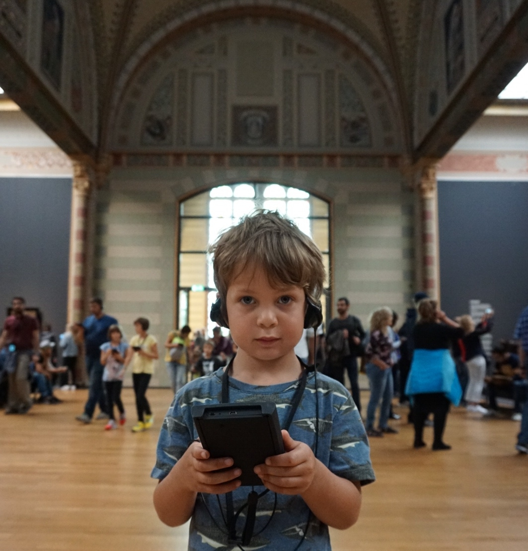 Museum Boy stares at the camera in the Rijksmuseum whilst he holds the family game and listens with headphones
