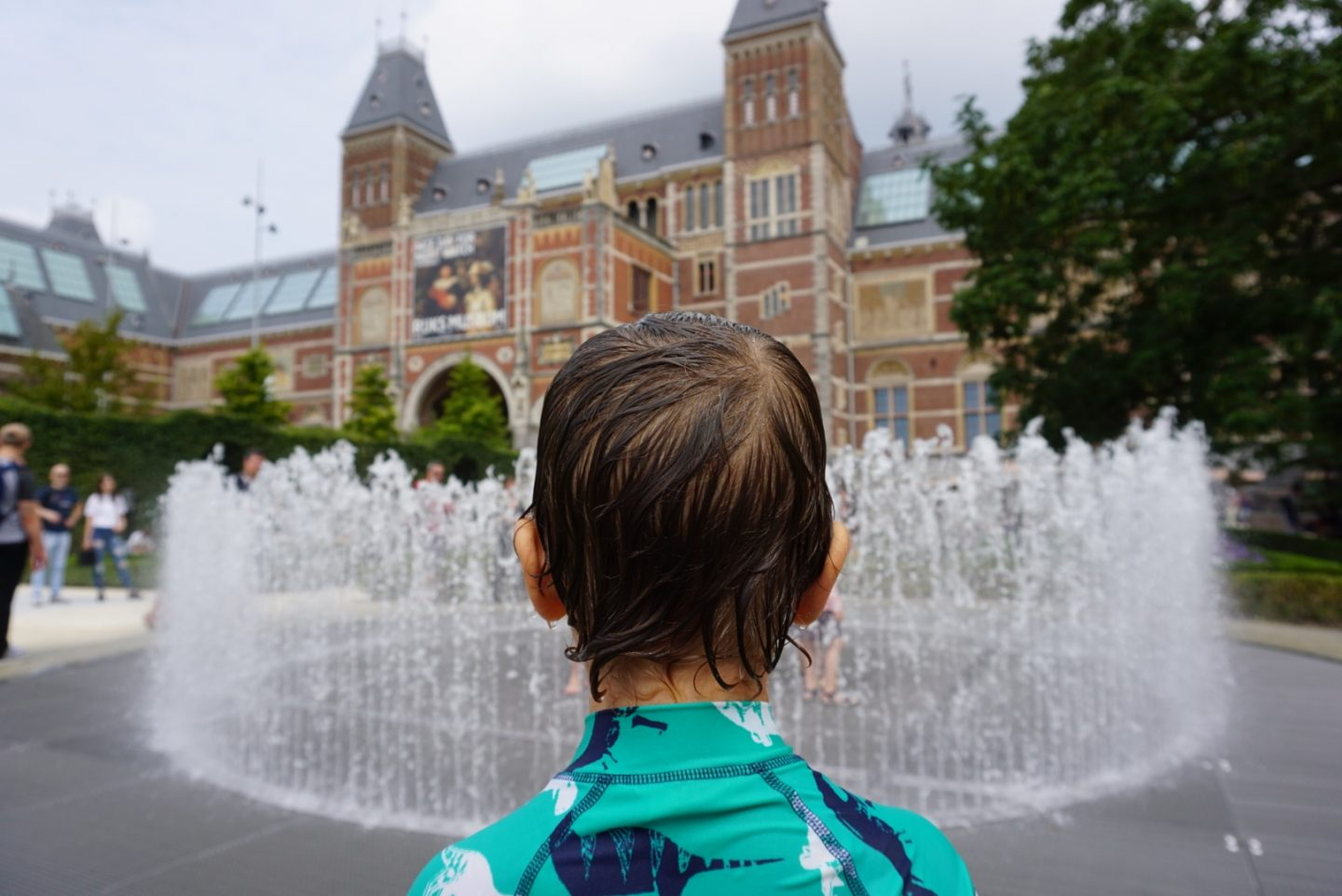 Museum Boy stares at the water fountains in front of the Rijksmuseum Amsterdam