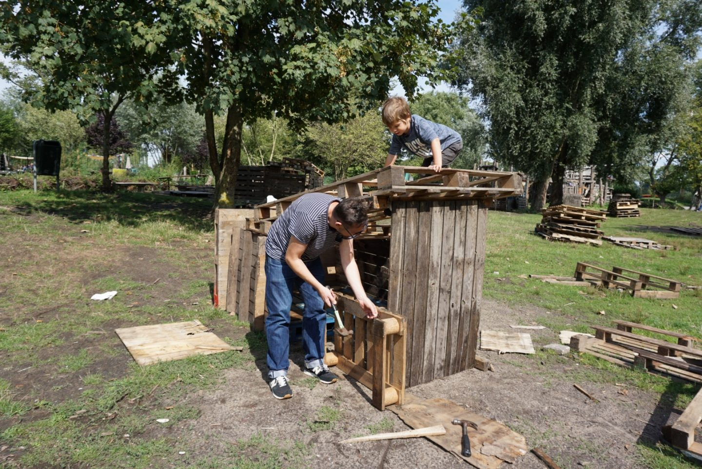Museum Boy and Museum Dad make a wooden play structure with hammer, nails and wooden pallets at Jeugdland, Amsterdam